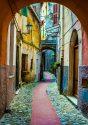 Narrow cobbled street in a European city seen through an archway